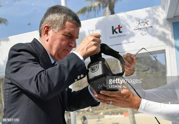 International Olympic Committee President Thomas Bach is given a VR headset as he tries virtual reality skiing complete with artificial snow falling...