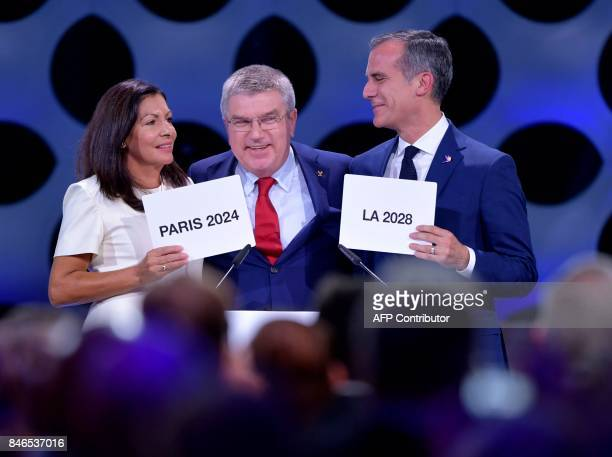 International Olympic Committee President Thomas Bach poses for pictures with Paris Mayor Anne Hidalgo and Los Angeles Mayor Eric Garcetti during the...