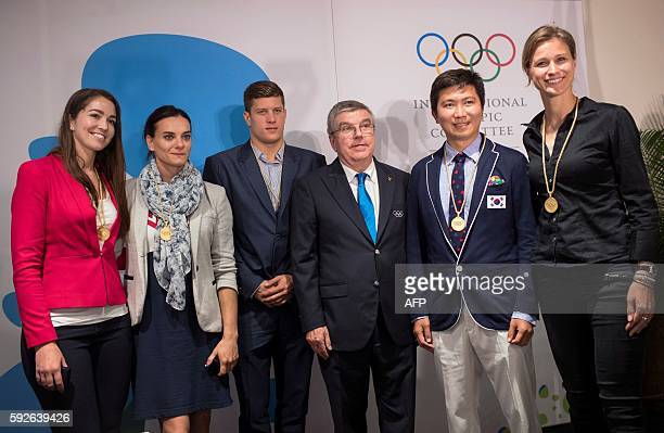 International Olympic Committee President Thomas Bach poses with newly elected members of the IOC Athletes Commission New Zealand BMX racer Sarah...