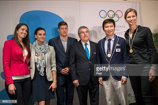 International Olympic Committee President Thomas Bach poses with newly elected members of the IOC athletes commission Sarah Walker of New Zealand...