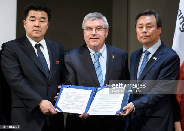 International Olympic Committee President Thomas Bach poses with North Korea's Sports Minister and Olympic Committee president Kim Il Guk and South...