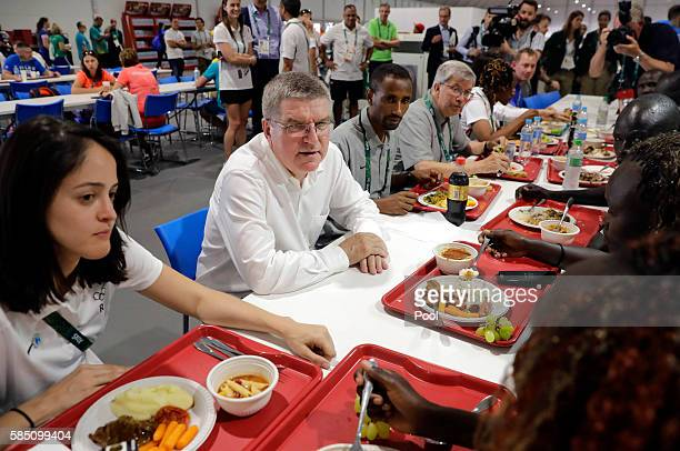 International Olympic Committee President Thomas Bach, second from left, chats with members of the Refugee Olympic Team as they eat lunch in athletes...