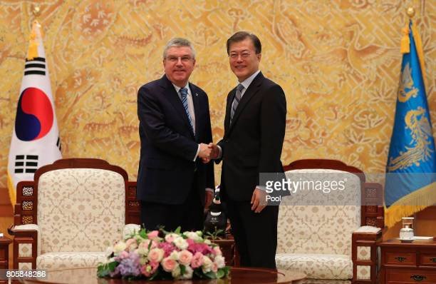 International Olympic Committee President Thomas Bach shakes hands with South Korean President Moon Jaein during their meeting at the presidential...