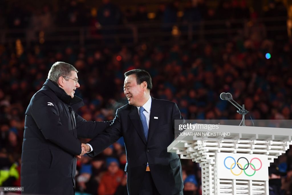 TOPSHOT - International Olympic Committee president Thomas Bach (L) shakes hands with Pyongchang 2018 Organising Committee president Lee Hee-beom during the closing ceremony of the Pyeongchang 2018 Winter Olympic Games at the Pyeongchang Stadium on February 25, 2018. / AFP PHOTO / Jonathan NACKSTRAND