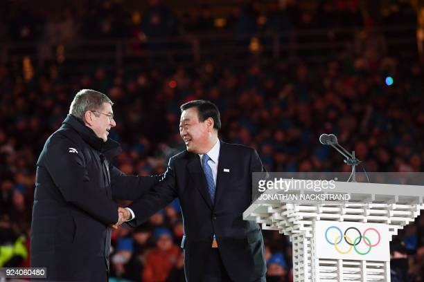 TOPSHOT International Olympic Committee president Thomas Bach shakes hands with Pyongchang 2018 Organising Committee president Lee Heebeom during the...