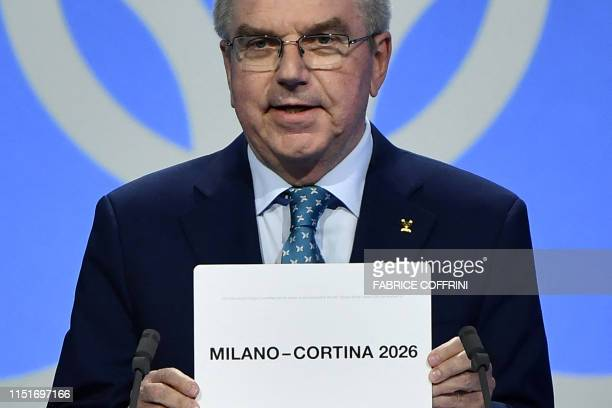 International Olympic Committee president Thomas Bach shows the card with the name Milan/Cortina d'Ampezzo as the winning name of the 2026 Winter...