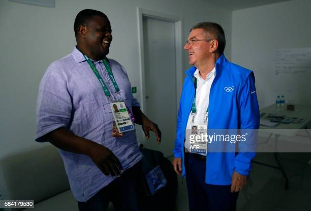 International Olympic Committee President Thomas Bach speaks with the leader of the Refugee Olympic Team, Robert Mutsauki, after moving into the...