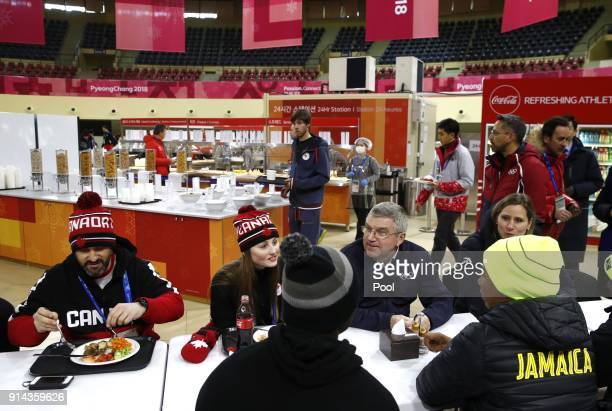 International Olympic Committee President Thomas Bach visits with members of the Canadian and Jamaican Olympic teams as they eat lunch during a tour...