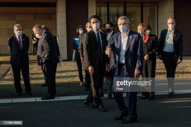 International Olympic Committee President Thomas Bach, wearing a face mask, gestures at journalists during a visit to the Olympic and Paralympic...