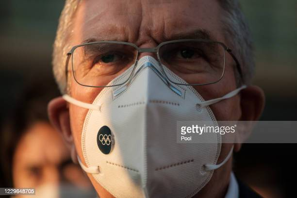 International Olympic Committee President Thomas Bach, wearing a face mask, talks to journalists during a visit to the Olympic and Paralympic Village...