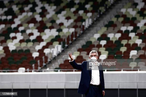 International Olympic Committee President Thomas Bach, wearing a face mask, gestures during a visit to the National Stadium, main venue for the...