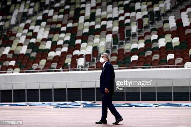 International Olympic Committee President Thomas Bach, wearing a face mask, visits the National Stadium, main venue for the postponed Tokyo 2020...