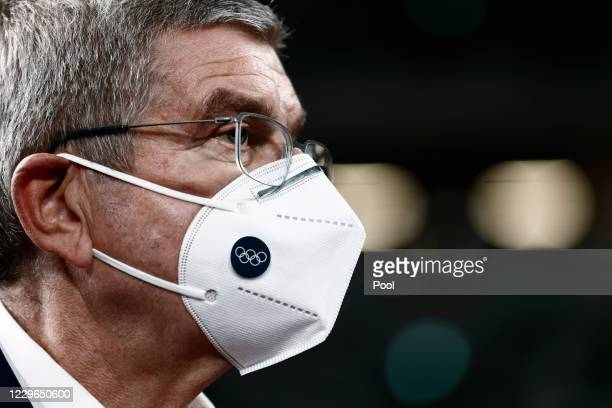International Olympic Committee President Thomas Bach, wearing a face mask, speaks to the media during a visit to the National Stadium, main venue...