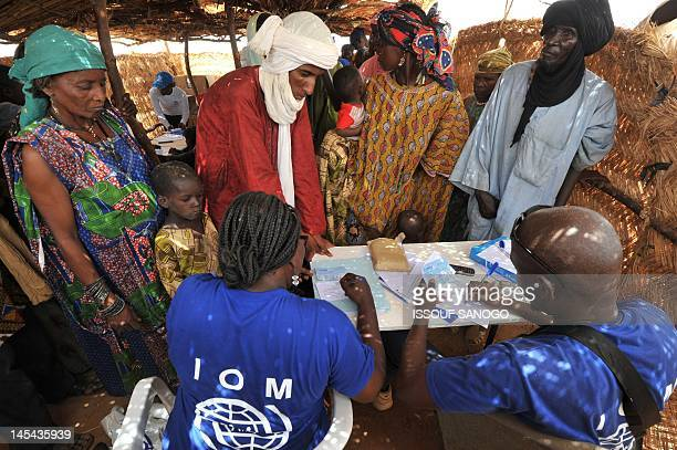 International Organization for Migration staff register refugees from northern Mali on May 29 2012 at the Imbaidou refugee camp near Ayoru 200 kms...