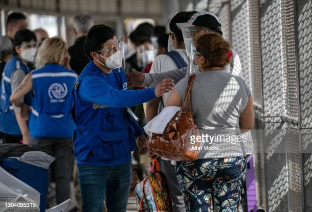 International Organization for Migration staffer congratulates immigrants at the U.S.-Mexico border as a group of at least 25 asylum seekers were...