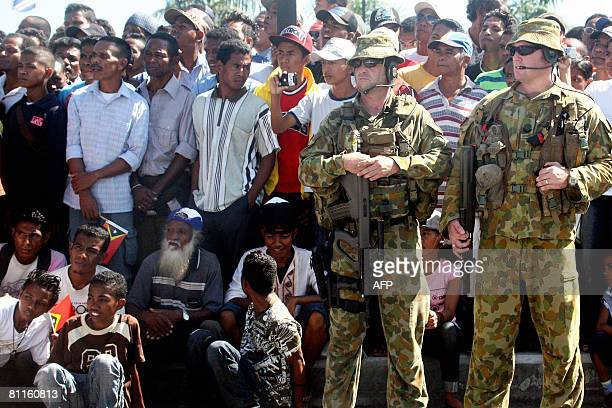 International peacekeeping soldiers from Australia keep vigil standing along with spectators watching a ceremony to mark country's Independence Day...