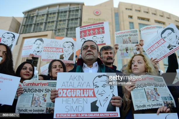 PEN International Policy and Advocacy Manager Sarah Clarke and protesters hold posters with images of Turkish daily newspaper Cumhuriyet staff...