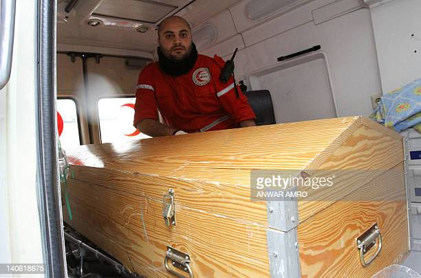 A International Red Crescent worker sits in an ambulance next to the coffin of American journalist Marie Colvin of the Sunday Times in Damascus on...