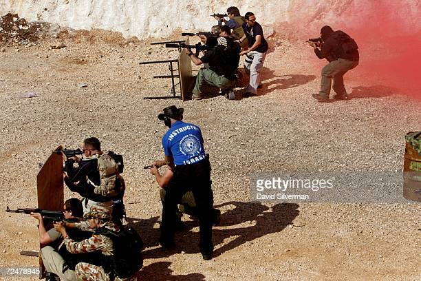 International Security Academy instructors Zafrir Pazi and Doron Balahsan supervise ISA trainees who open fire with assault weapons and handguns...