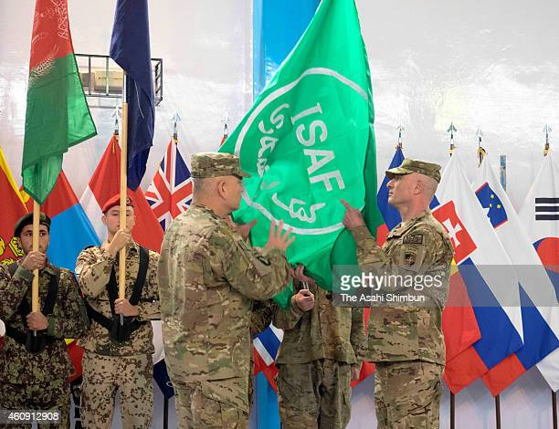 International Security Assistance Force commander General John Campbell folds the ISAF flag during a ceremony to mark the termination of the combat...