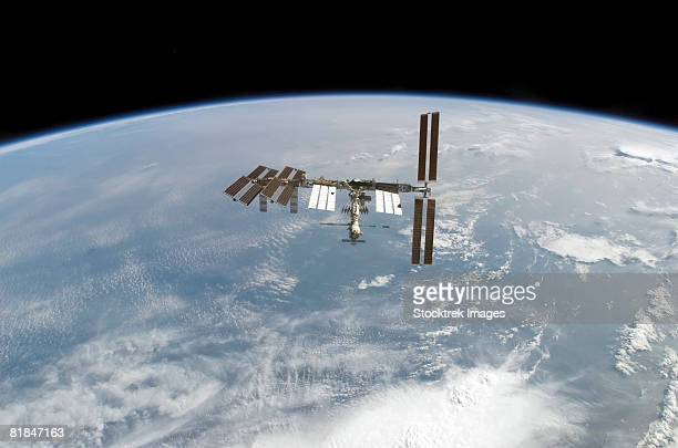 international space station backdropped by earth's horizon. - space station stock pictures, royalty-free photos & images