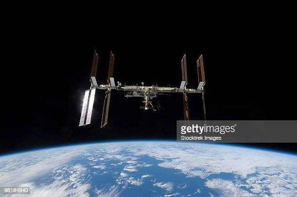 international space station backdropped by earth's horizon. - international space station stock pictures, royalty-free photos & images