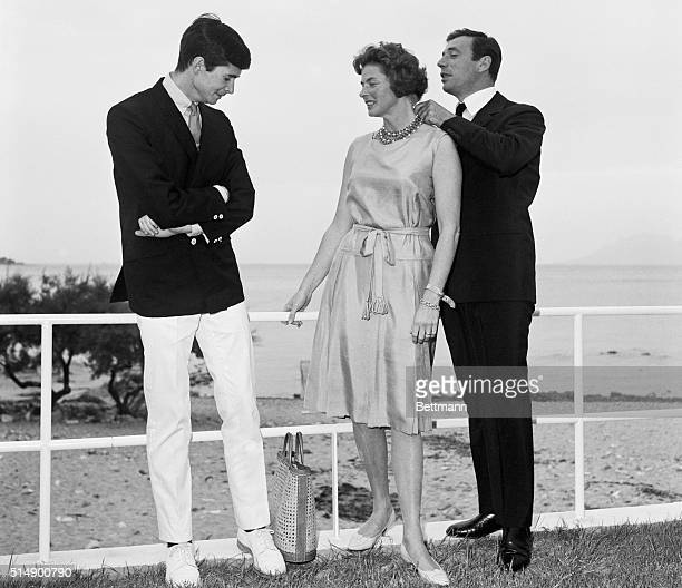 International Stars Canes France Anthony Perkins watches as Yves Montand adjusts a necklace on Ingrid Bergman after a luncheon attended by the stars...