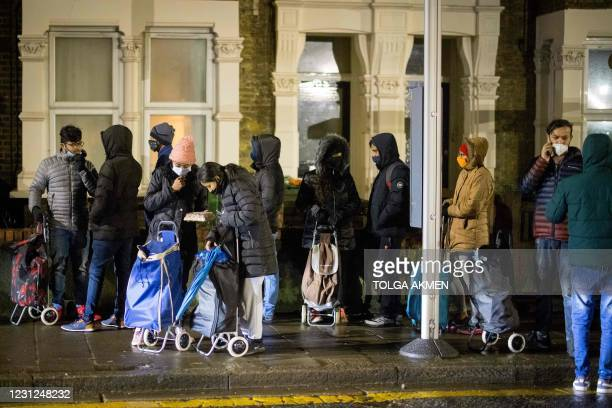 """International students queue to collect food packages at the Newham Community Project food bank in east London on February 16, 2021. - """"It's hard to..."""