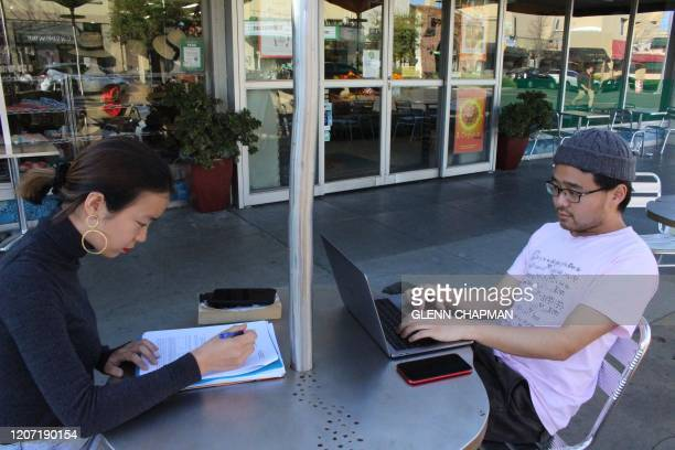 """International students Yaqing """"Victoria"""" Yang and Ende Shen of China study together at a sidewalk table in the Silicon Valley city of Palo Alto on..."""