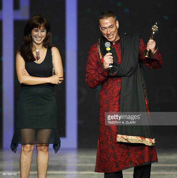 International Style Award winner actor Jean Claude Van Damme is presented his trophy by Kamal Dandona during the 2004 Bollywood Fashion Awards at the...