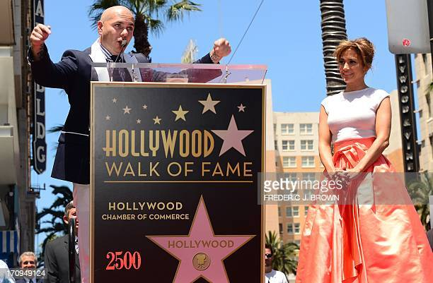 International superstar Jennifer Lopez looks on as Pitbull addresses the audience during the unveilng ceremony of her star in Hollywood California on...