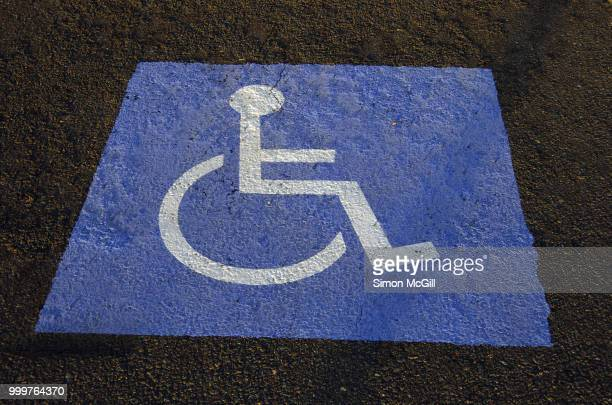 international symbol of access (isa), also known as the wheelchair symbol, on a parking space - disabled sign stock photos and pictures