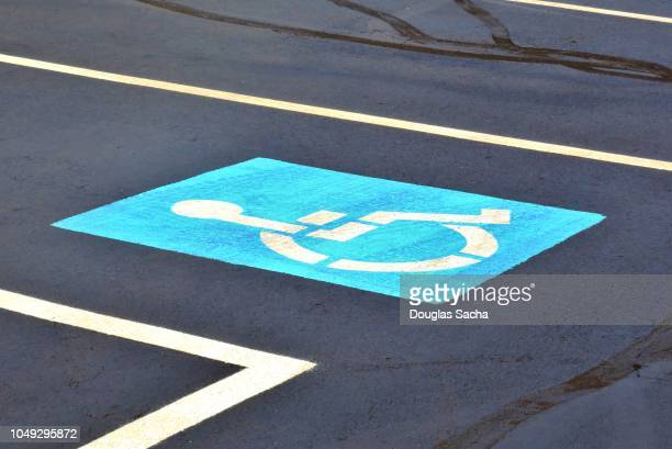 international symbol of handicap parking area painted on aparking lot - disabled sign stock photos and pictures