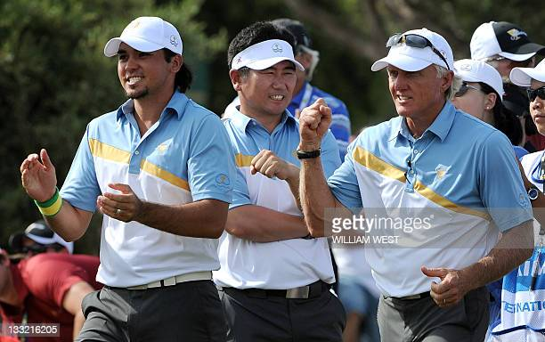 International team captain Greg Norman celebrates with his players YE Yang of South Korea and Jason Day of Australia on the second day of the...