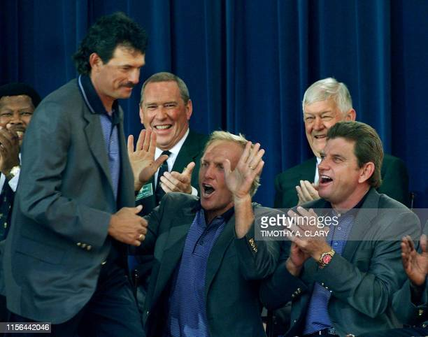 International Team player Carlos Franco is cheered on by teammates Greg Norman and Nick Price as he accepts his medal during the closing ceremonies...