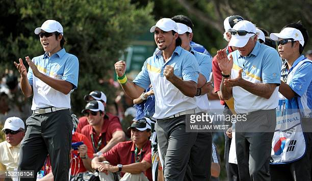 International team players Jason Day of Australia and KT Kim of South Korea celebrate with team captain Greg Norman after a team victory on the...