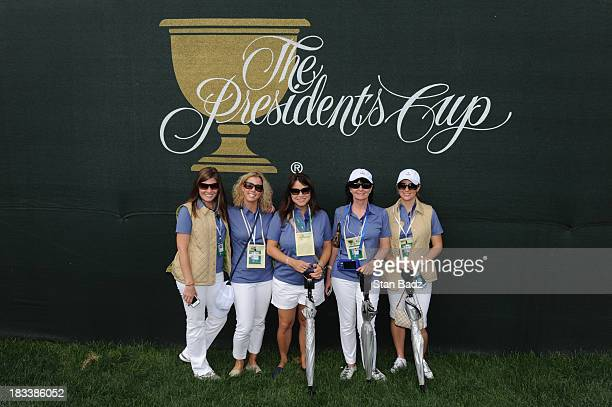 International Team wives and girlfriends pose for a photo on the first hole during the Day Two FourBall Matches of The Presidents Cup at the...