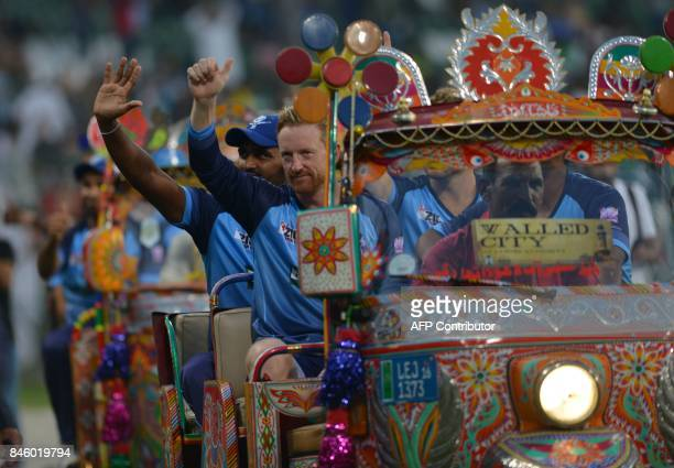 International World XI cricketer Paul Collingwood and teammates sit in an autorickshaw as they acknowledge the crowd at the main entrance of the...