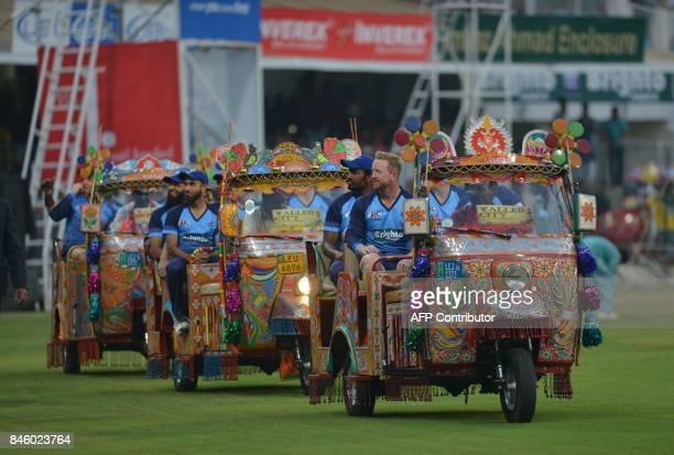 International World XI players sit in autorickshaws as they acknowledge the crowd at the main entrance of the Gaddafi Cricket Stadium in Lahore on...