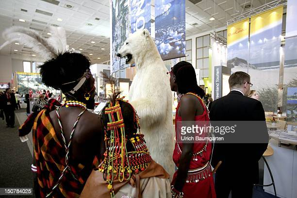 Internationale Tourismus Boerse ice bear at the presentation booth of Greenland in the front Africans with typical national costumes