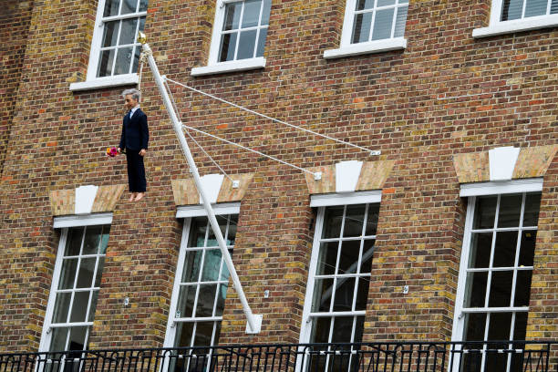 GBR: Internationally Renowned Artist Maurizio Cattelan Suspends A Sculpture Of A Hanging Man From A Flagpole In Mayfair's Savile Row