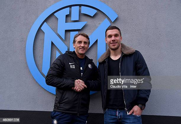 Internazionale head coach Roberto Mancini shakes hands with Lukas Podolski who is set to join the club on loan until the end of the season at Appiano...
