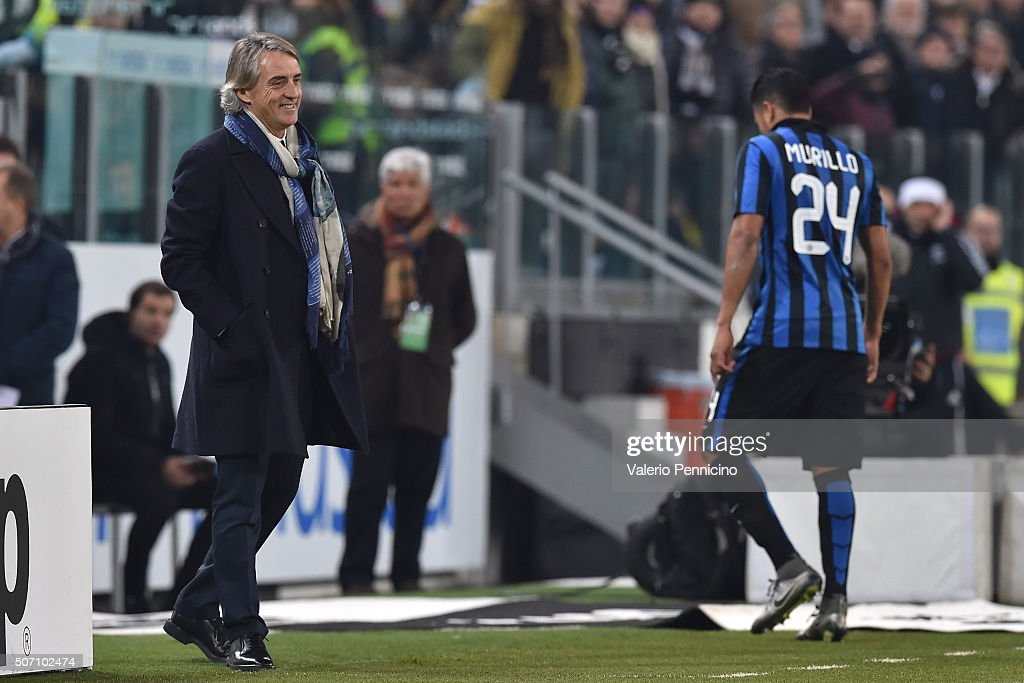 Internazionale Milano head coach Roberto Mancini (L) smiles after Jeison Murillo of FC Internazionale Milano walks off after receices a red card from referee Paolo Tagliavento during the TIM Cup match between Juventus FC and FC Internazionale Milano at Juventus Arena on January 27, 2016 in Turin, Italy.