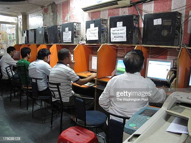 Internet 001 005 031 Indians browse the internet in cyber cafes next to large signs that tell them that their log data is being recorded and they are...