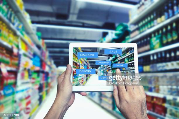 Internet and Online Shopping Concept Present by Hand With E-Commerce Icon Above on supper market  Background