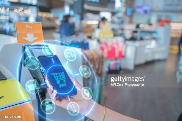 internet of things and mobile payment concept,close up hand holding smart phone with communication icons.paying through terminal.connection and wireless network technology - financial technology stock pictures, royalty-free photos & images