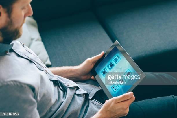Sakernas Internet kontrolleras av appen på digitala tablett i vardagsrum