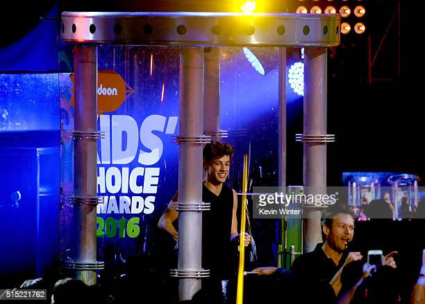 Internet personality Cameron Dallas stands in a slime tank as host Blake Shelton speaks onstage during Nickelodeon's 2016 Kids' Choice Awards at The...