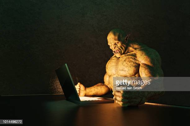 internet troll: angry ogre pounding fists on desk while using laptop computer - rasend vor wut stock-fotos und bilder