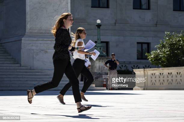 Interns run opinions to colleagues in front of the US Supreme Court in Washington DC US on Monday June 25 2018 The US Supreme Court threw out a...